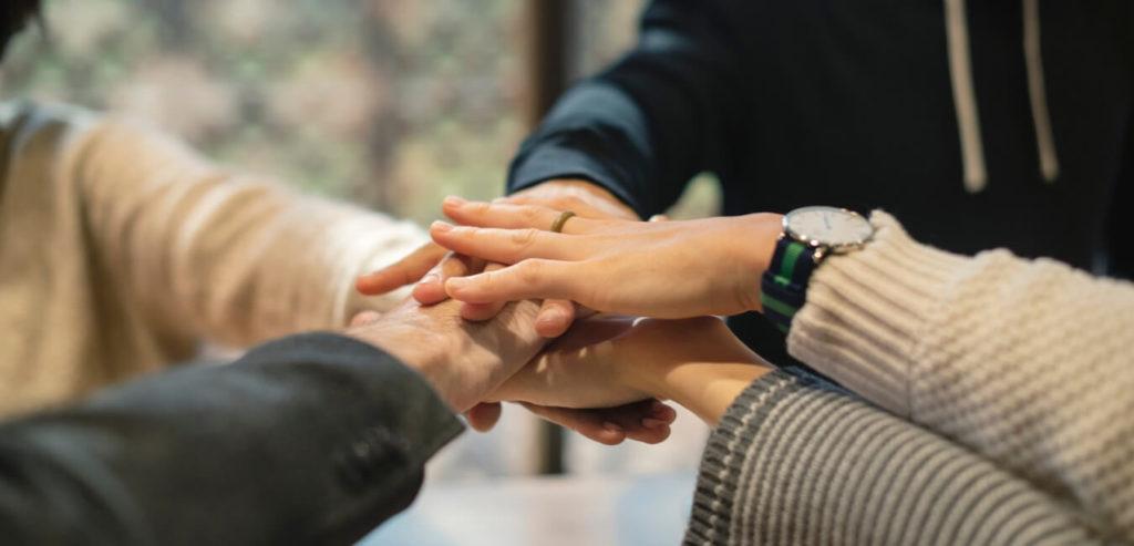 手を重ねて仲間で協力の意志を確認