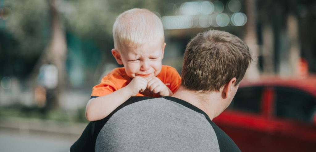 泣いている赤ちゃんを抱っこする親