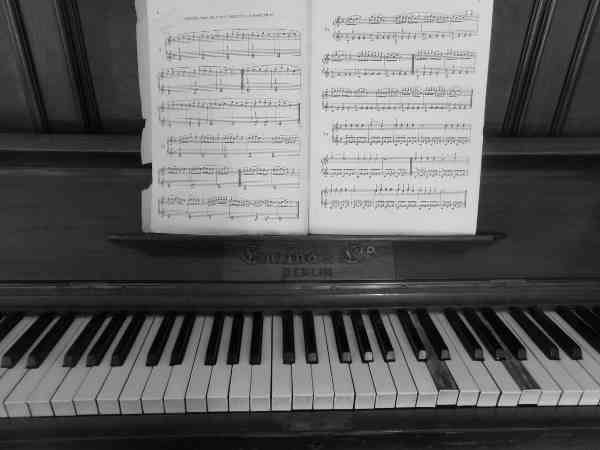 楽譜が譜面台に乗っているピアノ