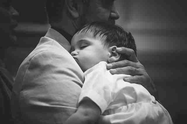 寝ている赤ちゃんを抱っこしている男性