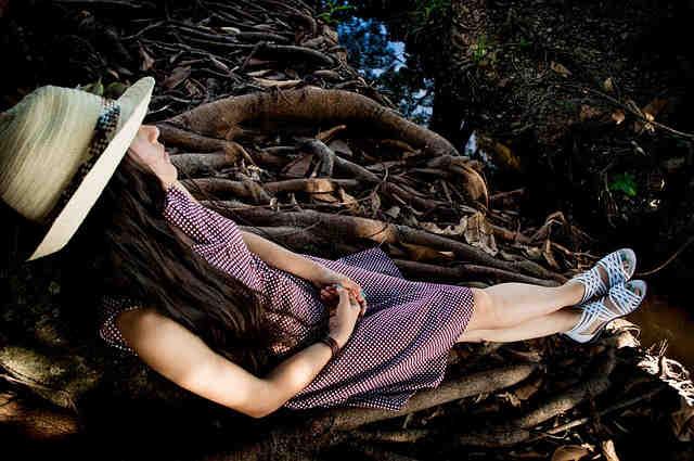 木の根元で寝る女の子