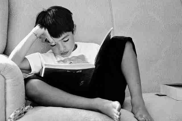 ソファで本を読む男の子