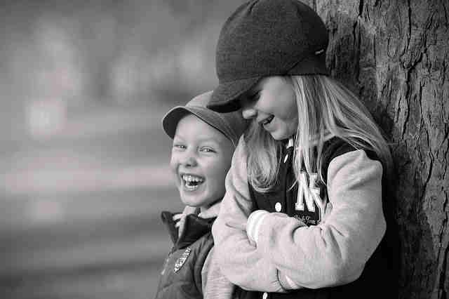 木によりかかって笑っている2人の女の子
