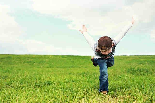 草原でポーズをとる男の子