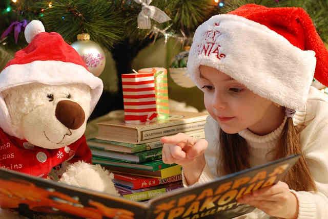 クリスマスにくまのぬいぐるみと絵本を読む女の子