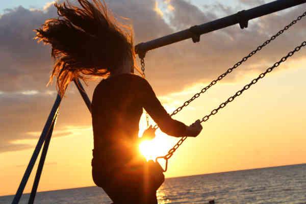 海辺でブランコをする女の子
