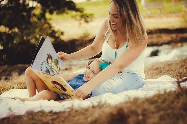 公園で絵本を読んでもらう子供と絵本を読む大人