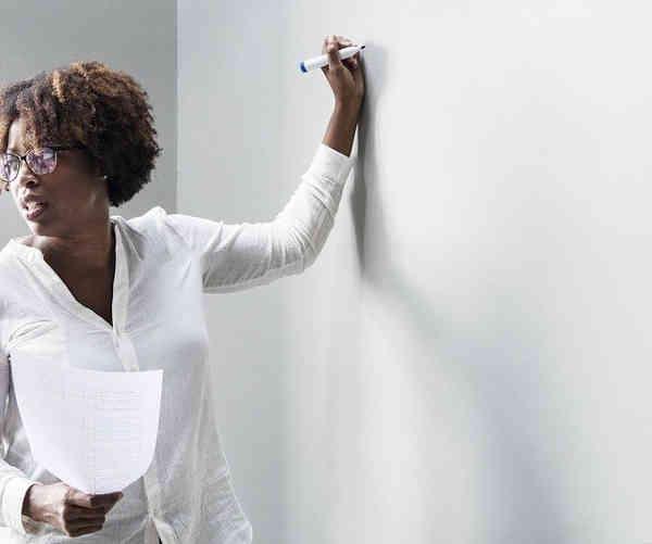 ホワイトボードに字を書く学校の先生
