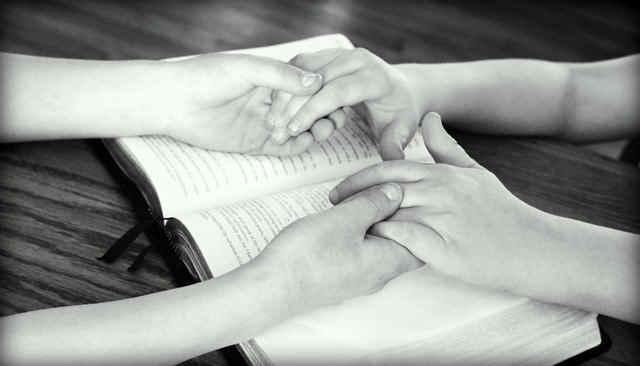本の上で手を取り合う2人の子供
