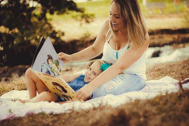 親に絵本を読んでもらっている女の子