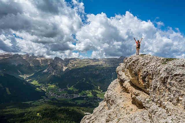 山の頂上で手をあげる女性