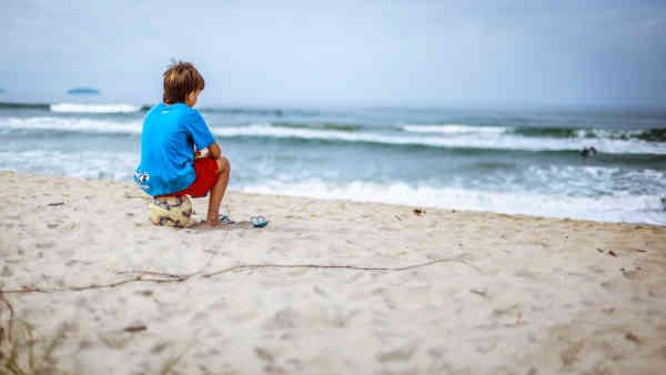 海でサッカーボールに座る孤独な少年