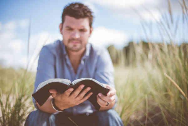 草むらで本を読む男性