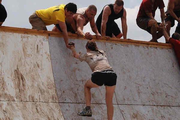 壁を登る女性と助ける男性たち
