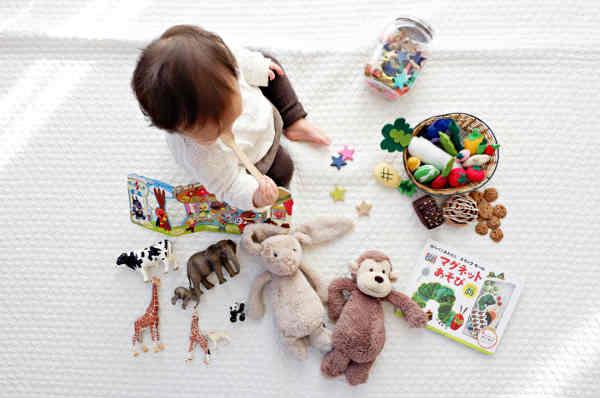 おすわり時期の赤ちゃんと絵本や数々のおもちゃ