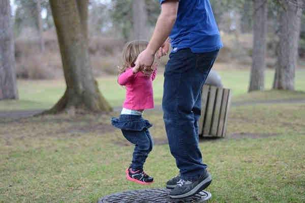 父親とジャンプする女の子